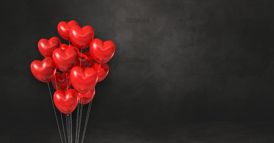 Red heart shape balloons bunch on a black wall background. Horizontal banner.