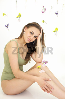 Crop woman with flowers on knees