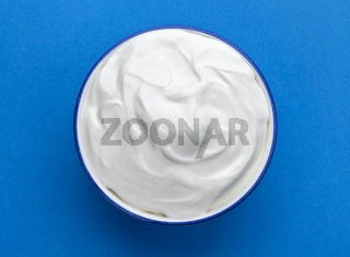 Bowl of sour cream on blue background