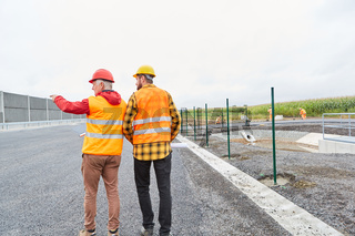 Bauarbeiter bei Begehung von Baustelle im Straßenbau