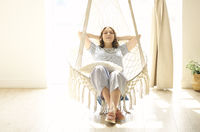Woman relaxing in hanging chair at home