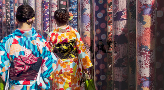 Woman in traditional dress visiting kimono forest with poles with kimono fabrics at Arashiyama Station in Kyoto, Japan
