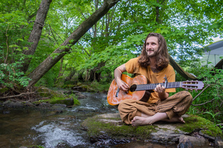 Hippie playing music on the shore of a river