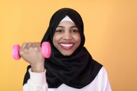 afro muslim woman promotes a healthy life, holding dumbbells in her hands