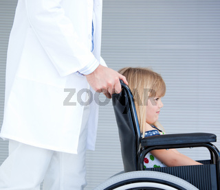 Smiling little girl sitting on the wheelchair supported by a doctor