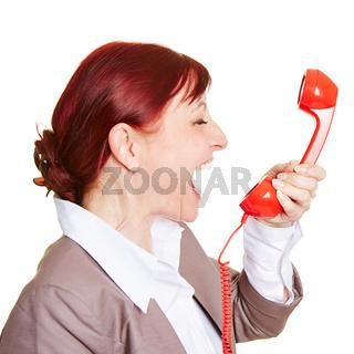 Wütende Geschäftsfrau schreit in Telefonhörer