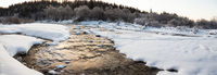 Water flowing between ice and snow in a river in winter