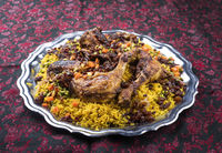 Traditional fried Arabic chicken majboos with chicken leg and jeweled rice served as close-up in a rustic oriental tray
