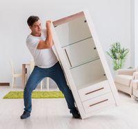 Man moving furniture at home