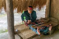 Old woman sew in traditional tribal dress