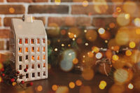 Christmas candle in form of house or home, blurred Christmas fir tree lights