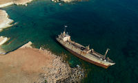 Aerial drone view of an abandoned ship moored at the coastal rocky area.
