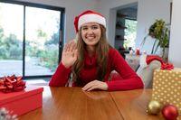 Happy caucasian woman wearing santa hat having video call at christmas time
