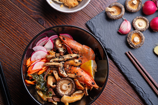 miso soup with mussels, shrimps , shiitake mushrooms and vegatables. served at dark brown wooden table. flat lay