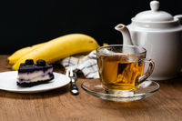 View of hot tea in transparent cup and slice of blueberry cheesecake in white ceramic dish.