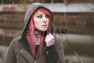 thoughtful portrait of young woman with piercings and tattoos