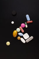 Colorful pills, tablets and capsules on black background.