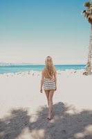 Back of long-haired young woman walking on the beach in sunny day. Vertical.
