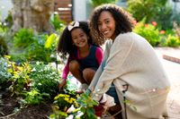 Happy african american mother and daughter planting flowers