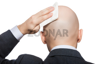 Hand holding tissue wiping or drying bald sweat head