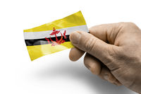 Hand holding a card with a national flag the Brunei