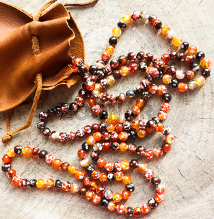 Sunny beads of amber fireplace faceted agate with leather jewelry pouch bag on rustic background