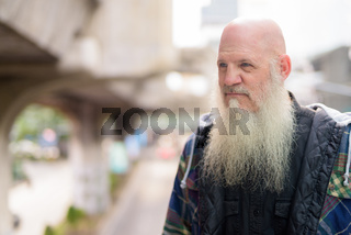 Mature bald hipster man with long beard thinking in the city streets