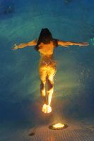 Athletic adult female swimming underwater in pool with geothermal water illuminated by night lights. High-angle shot