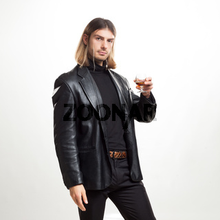 Portrait of young man blond hair with a glass of brandy, posing over gray background. Classic style. Studio shot