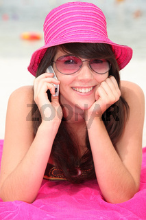 Girl in a shocking pink hat making a call on the beach