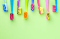 New Toothbrushes Set On Green Paper Background