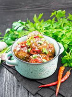 Meatballs in sweet and sour sauce on wooden board