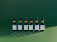 Row of luxury essential oils bottles with empty label. 3d render in trendy emerald and gold style colours. Refillable packaging solutions.