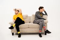 Two handsome guys had a fight while sitting on opposite sides of the sofa. Group of friends are sitting on a soft couch and communicates isolated on white background