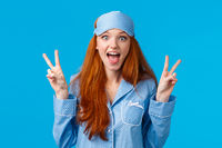 Excited cute redhead girl in sleep mask and pyjama showing peace signs and screaming thrilled overwhelmed positive emotions, standing amused over blue background wearing nightwear