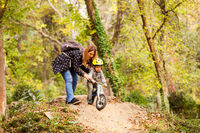Supportive mom encourages boy to ride down the hill