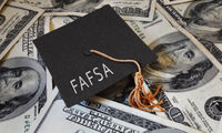 FAFSA (Free Application for Federal Student Aid) text on graduation cap and money - financial aid concept