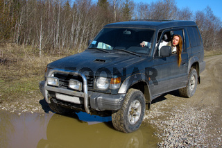 Young woman behind rudder of offroad car on dirt road before water obstacle