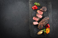 Barbecue dry aged wagyu roast beef steak with paprika and zucchini offered as top view on a charred wooden board with copy space left