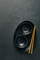 Pottery bowls or ceramics in blacke tone with chopsticks on black background. Kitchenware