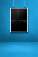 Black folded poster hanging on a blue wall with clips