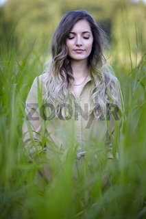 Young blonde woman is standing in tall grass with closed eyes.