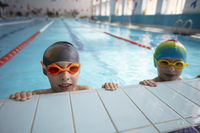 Boy in a swimming cap and swimming goggles in the pool. The child is engaged in the swimming section.