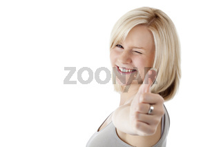 Attraktive blonde Frau hält zuzwinkernd Daumen nach oben.Freigestellt auf weissem Hintergrund.
