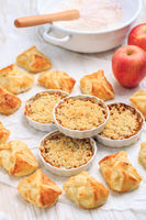 Homemade apple turnovers and small apple crumble cakes with ingredients