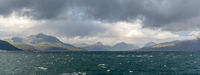 A panorama view of a rugged and wild coastline with mountains and stormy seas with whitecaps under and expressive cloudy sky