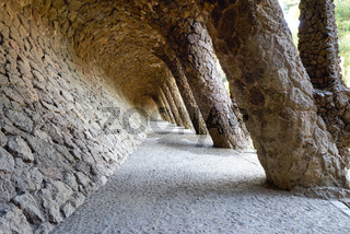 Barcelona. Catalonia. Spain. A colonnaded pathway in Park Guell, designed by Antoni Gaudi