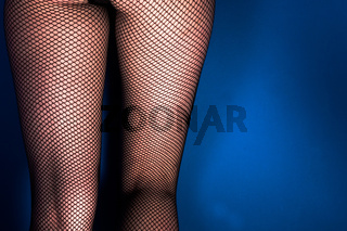 Girl in stockings against blue wall