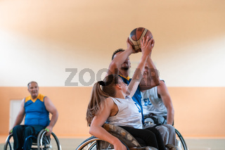 Disabled War veterans mixed race and age basketball teams in wheelchairs playing a training match in a sports gym hall. Handicapped people rehabilitation and inclusion concept