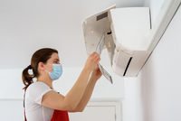 Female technician wearing face mask and cleaning air conditioner